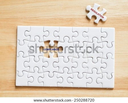 Compliance and Regulation words written on white jigsaw puzzle,business concept background - stock photo