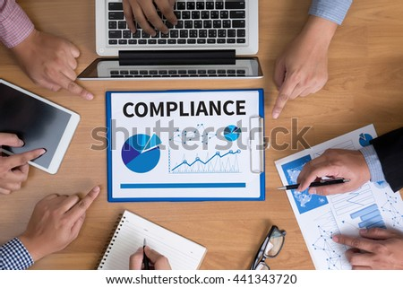 COMPLIANCE Business team hands at work with financial reports and a laptop, top view - stock photo