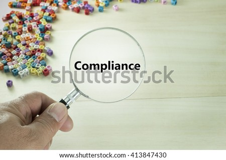 Compliance text written on magnifying glass - stock photo