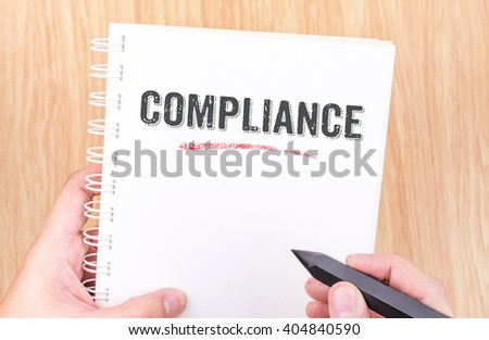 Compliance word on white ring binder notebook with hand holding pencil on wood table,Business concept. - stock photo