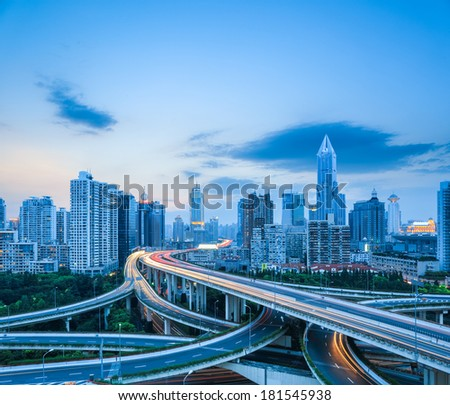 complicated highway intersection with modern city skyline at dusk in shanghai , road transportation infrastructure.  - stock photo