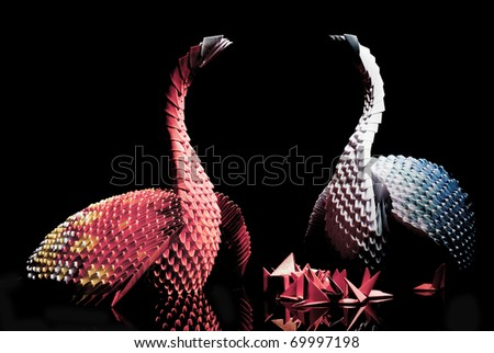 Complicated origami paper model of  swan, on black background - stock photo