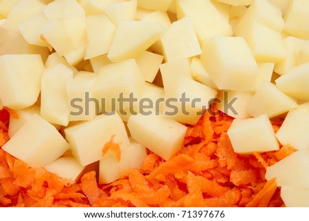 Components for soup: grated crude carrots and the crude potato cut with cubes - stock photo