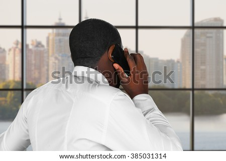Composed phone conversation. Phonetalk next to a window. Executive is negotiating. Daytime negotiation in the city.