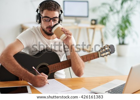 Composer drinking take-out coffee when working on new song