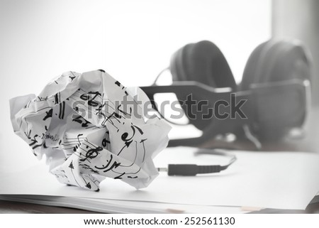 composing music concept with shallow DOF evenly matched jack of headphone and crumpled musical notes paper - stock photo