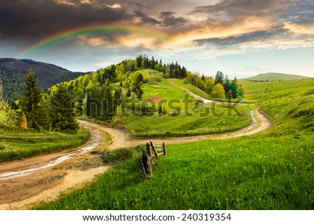 composite autumn landscape. fence near the cross road on hillside meadow in mountains. few fir trees of forest  on both sides of the road in morning light with rainbow - stock photo
