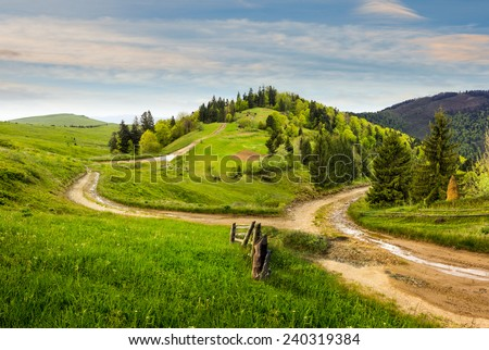 composite autumn landscape. fence near the cross road on hillside meadow in mountains. few fir trees of forest  on both sides of the road in morning light - stock photo