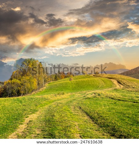 composite autumn landscape. path through the meadow on mountain top in morning light with rainbow