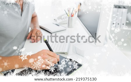 Composite image of a Casual male photo editor using graphics tablet against fir tree forest and snowflakes - stock photo