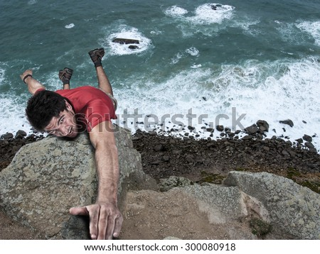 Composite image of an adventure rock climbing man dangling from a cliff - stock photo