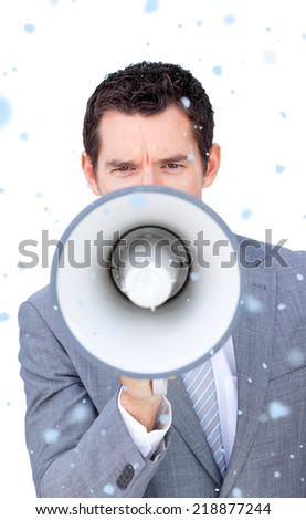 Composite image of Angry businessman shouting through a megaphone with snow falling - stock photo