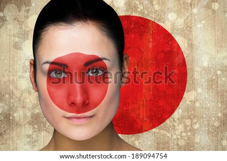 Composite image of beautiful football fan in face paint against japan flag in grunge effect
