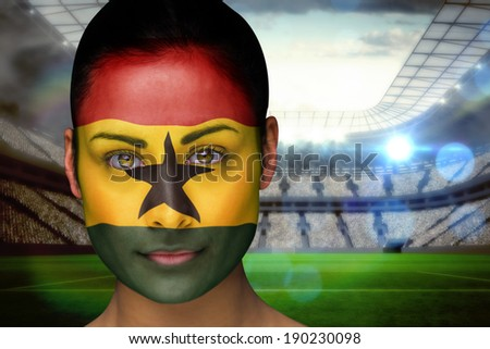 Composite image of beautiful ghana fan in face paint against vast football stadium with fans in white - stock photo