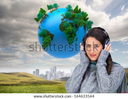 Composite image of beautiful model wearing winter clothes listening to music - stock photo