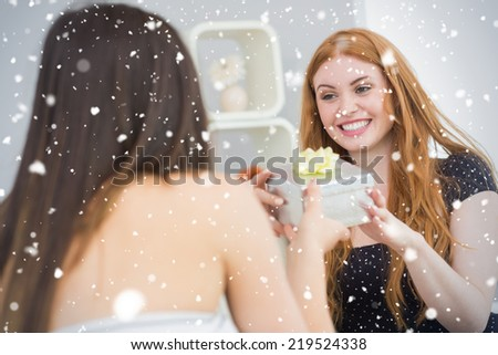 Composite image of Beautiful young blond receiving a gift box on sofa against snow falling - stock photo