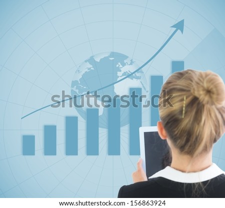 Composite image of blonde businesswoman holding tablet in front of blue global background showing statistic - stock photo