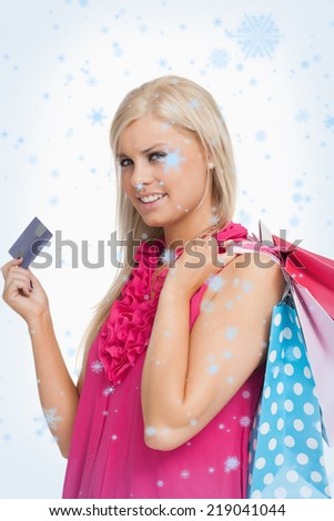 Composite image of Blonde holding shopping bags and a card with snow falling
