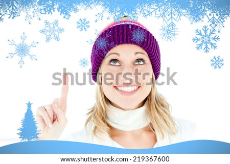 Composite image of Bright woman with a colorful hat pointing upwards with snow flake frame in blue