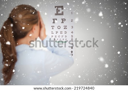 Composite image of brunette woman making an eye test against snow falling - stock photo