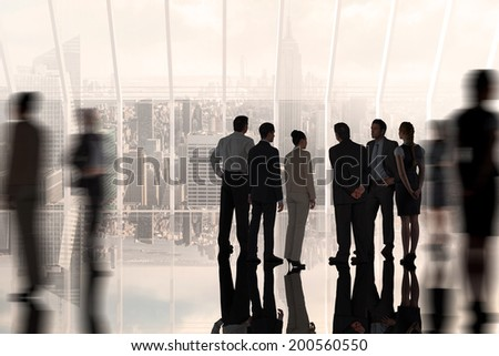 Composite image of business colleagues standing against room with large window looking on city - stock photo