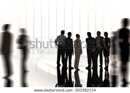 Composite image of business colleagues standing against white room with large window overlooking city - stock photo