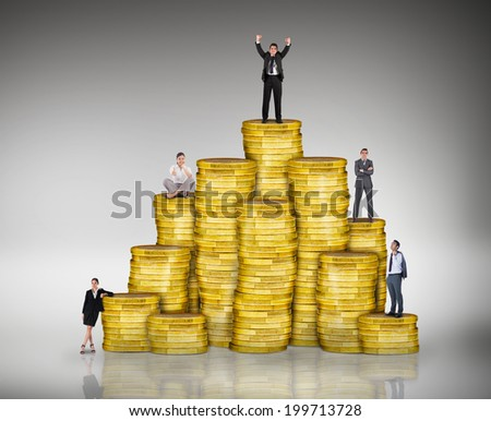 Composite image of business people on pile of coins against grey vignette - stock photo