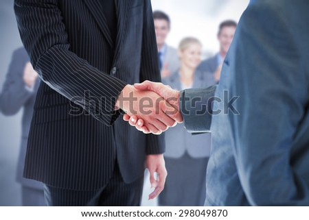 Composite image of business people shaking hands - stock photo