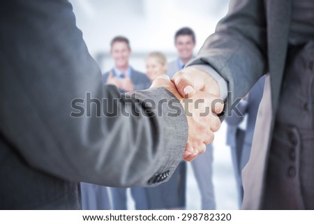 Composite image of business people shaking hands close up - stock photo