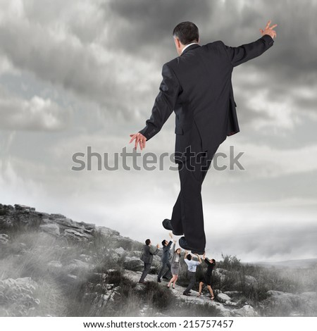 Composite image of business team supporting boss against rocky landscape
