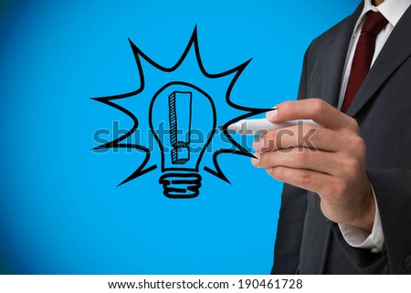 Composite image of businessman drawing light bulb against blue background with vignette