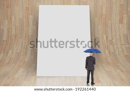Composite image of businessman holding umbrella against white card - stock photo