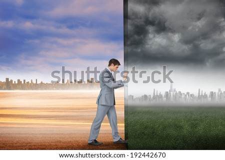 Composite image of businessman pushing away scene of city on the horizon