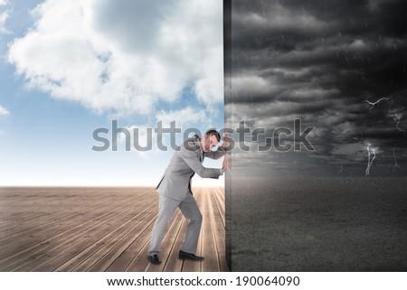Composite image of businessman pushing away scene of ominous landscape - stock photo