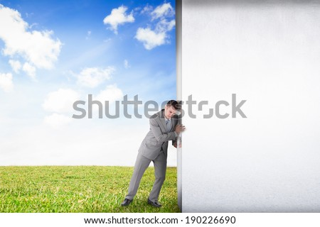 Composite image of businessman pushing away scene to serene landscape