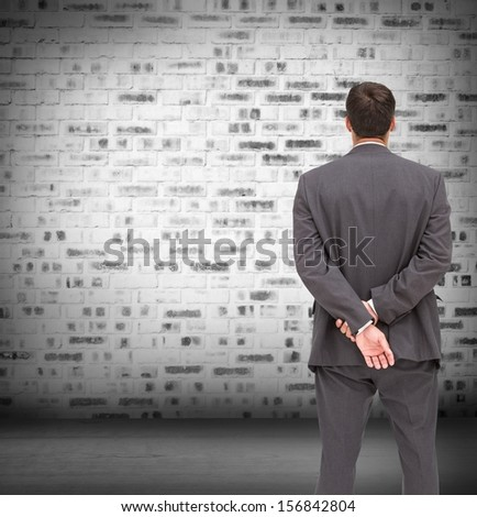 Composite image of businessman standing with hands behind back looking at brick lined wall - stock photo