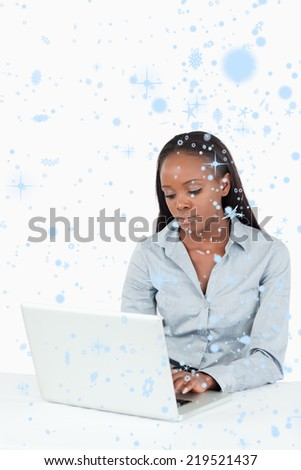 Composite image of Businesswoman using a laptop with snow falling