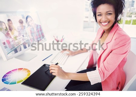 Composite image of casual female photo editor using computer - stock photo