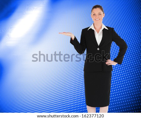 Composite image of charming woman in suit showing a copy space while standing - stock photo