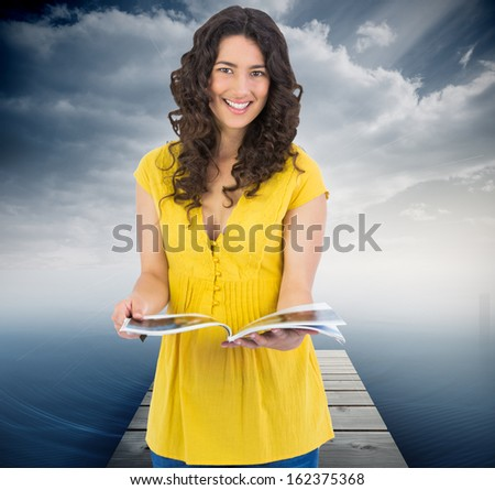 Composite image of cheerful curly haired brunette reading magazine - stock photo