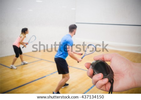 Composite image of coach is holding a stopwatch against couple enjoying a game of squash - stock photo