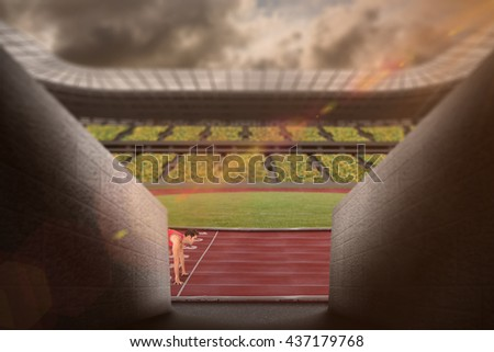 Composite image of confident male athlete in ready to run position in a stadium - stock photo