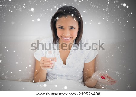 Composite image of content young dark haired model taking medication against snow