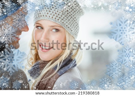 Composite image of couple in warm clothing hugging against snow