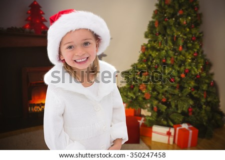 Composite image of cute little girl wearing santa hat - stock photo