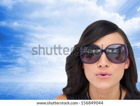 Composite image of elegant brunette wearing sunglasses sending kiss to camera on sky background