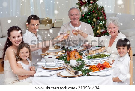 Composite image of Family drinking a toast in a Christmas dinner against snow falling