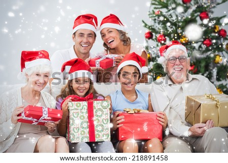 Composite image of Family exchanging christmas presents against snow falling - stock photo