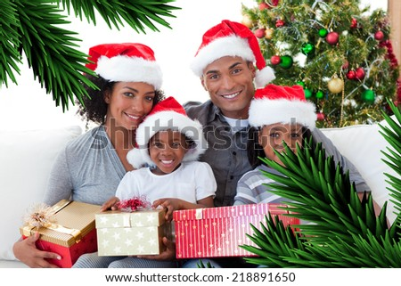 Composite image of family holding Christmas presents against digitally generated fir tree branches - stock photo