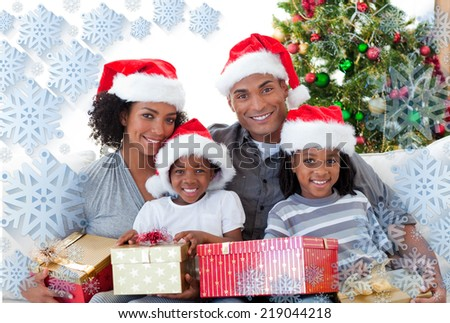 Composite image of family holding Christmas presents against snowflake frame